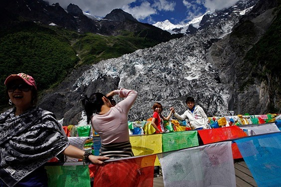 China, 2009  Tourists snap memories against the dirty, melting ice of Mingyong Glacier in China's Yunnan Province. As temperatures have warmed, the glacier has receded a third of a mile over the past decade, and its meltwater is no longer drinkable.