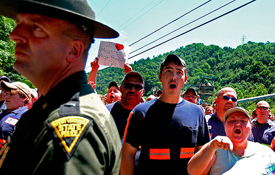 Coal miners and wives guard the entrance to a Massey Energy mountaintop mine, shouting at protesters who had marched there to demand a stop to mountaintop removal mining. Nearly 2,000 miles of streams have been contaminated or buried and more than a million acres of forest have been destroyed across Appalachia due to mountaintop coal mining. Each week, four million pounds of explosives are used in the region for mountaintop removal, the equivalent of the bomb dropped on Hiroshima. Coal proponents argue that America needs mountaintop mining to keep the lights on, and West Virginia needs it for the jobs.