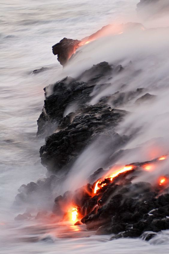 Pahoehoe lava flows to the coast, cooling into a hardened, fan‐shaped shelf called a lava delta or lava bench. As long as a supply of molten lava continues to flow, outpacing the destruction of the waves, new land continues to creep seaward.