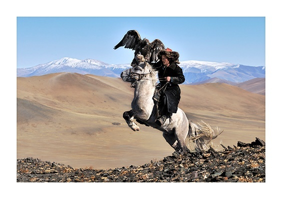 Olgii Province, Mongolia A hunter and his eagle astride his white horse.