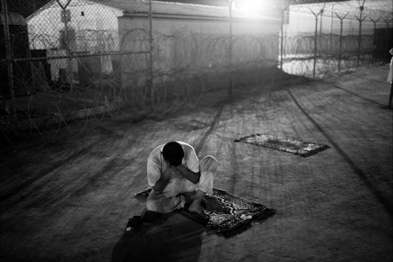 An Iraqi detainee sits on a prayer rug in a holding pen in Camp Bucca, resting his head in his hands. Camp Bucca is a U.S. holding facility in the vicinity of Umm Qasr, Iraq, with more than 18,500 Iraqi detainees. The vast, city-like compound is releasing detainees by the hundreds every week, hoping to empty the facility in a year.