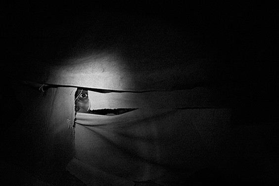 Gulu'A boy peeks through the hole in the MSF/Doctors Without Borders refugee camp in the Gulu district of Northern Uganda.