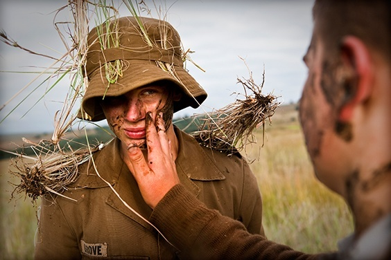"""A boy puts mud on another boy's face as camouflage during a nine day camp. - from the series """"Afrikaner Blood"""""""