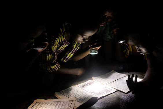 """From """"Life without Lights"""" Children read the Koran by flashlight at a mosque in Wantugu, Northern Region, Ghana, 2007. Wantugu had power lines installed in 2000, but government officials failed to connect them to a power source. The series documents global energy poverty among some of the 1.4 billion people in the world who live without access to electricity."""