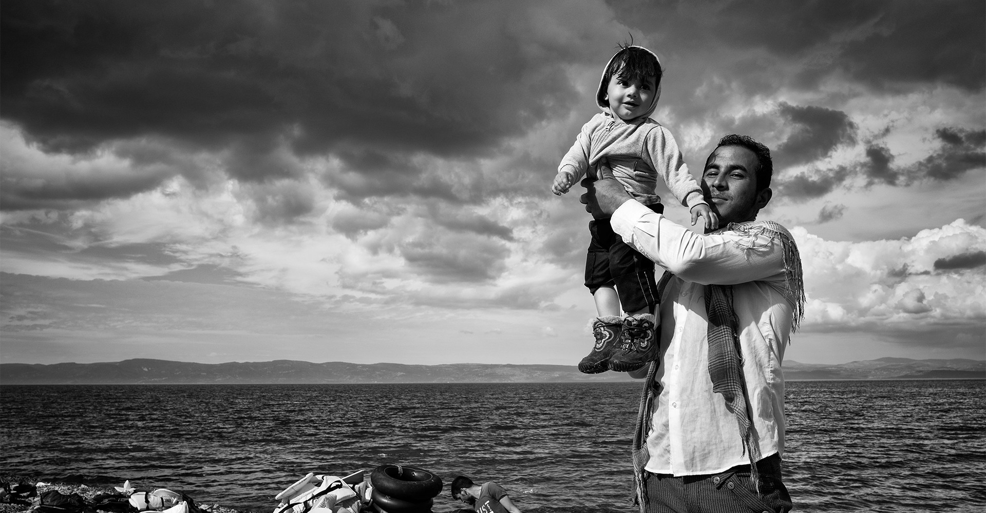 Lesbos, Greece, October 2015: A father celebrates with his child on the Greek island of Lesbos after a stormy crossing with his family over the Aegean Sea from Turkey.