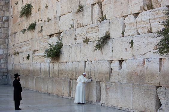 On May 26, 2014, the final day of a two-day visit to the Holy Land, Pope Francis visited the Western Wall in Jerusalem, standing in prayer before tucking a note into a crevice. Originally built as a retaining wall for a temple, the towering bricks have become a pilgrimage site for Jews, Christians, and Muslims, alike, uniting these three Abrahamic religions.
