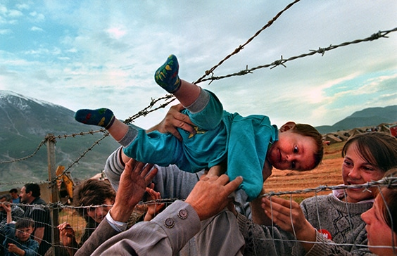 "In 1998, after a decade of increasing tension in Kosovo, violence by Serbian and Yugoslav forces against ethnic Albanians led to a wave of refugees fleeing the country. Sometimes separated families found each other; Carol Guzy captured such a moment at a United Arab Emirates-run camp in Kukes, Albania. Guzy recalled, ""It's actually a joyful photo. Families that had escaped ethnic cleansing did not know if their loved ones had survived or not; [they] were lined up along that fence.""  The Shala family from Prizren, Kosovo found each other at the fence and passed 2-year-old Agaim Shala through the barbed wire barrier so he could visit with his relatives.  Originally trained as a nurse, Carol Guzy has become known for unflinching but intensely empathetic photographs that capture scenes of conflict and destruction. She is the only person to win four Pulitzer Prizes for journalism, including the one awarded for this photograph."